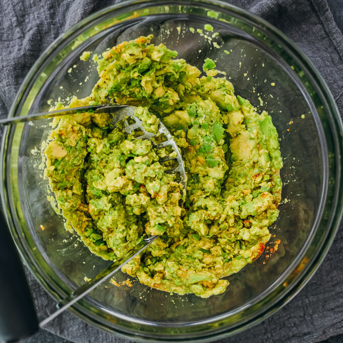 mashing avocado with seasonings