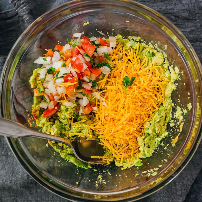 adding cheese and pico de gallo to guacamole