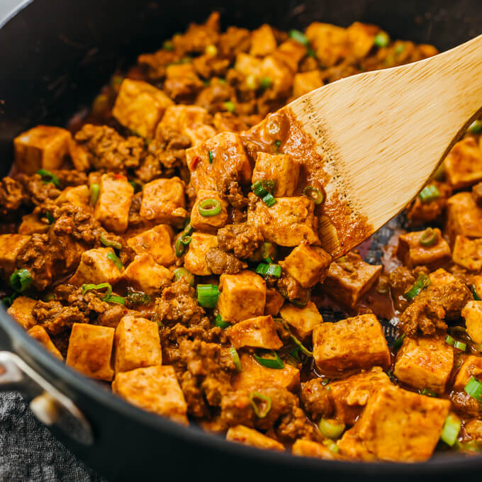 close up view of stirring mapo tofu in skillet