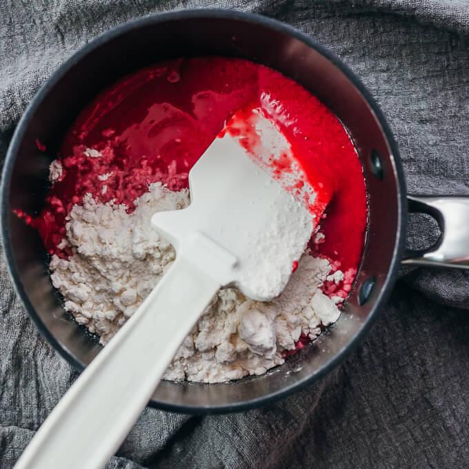 stirring raspberry puree with sweetener