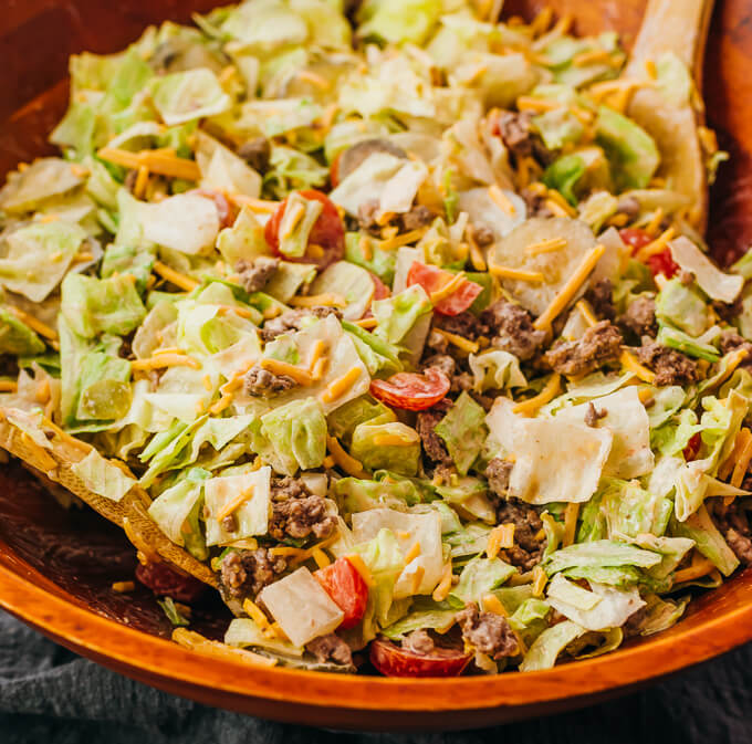 tossing big mac salad in wooden bowl