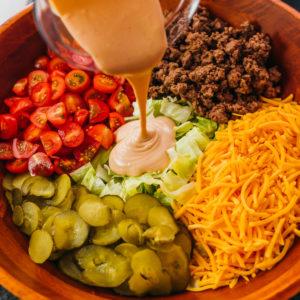 pouring dressing over big mac salad