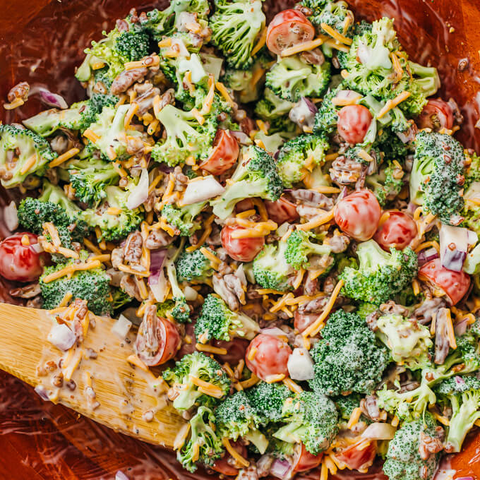 stirring broccoli salad with dressing