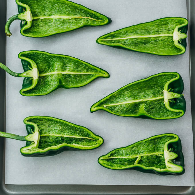 halved poblano peppers on baking sheet