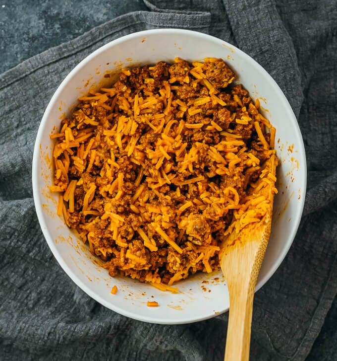 stirring beef mixture with shredded cheddar cheese