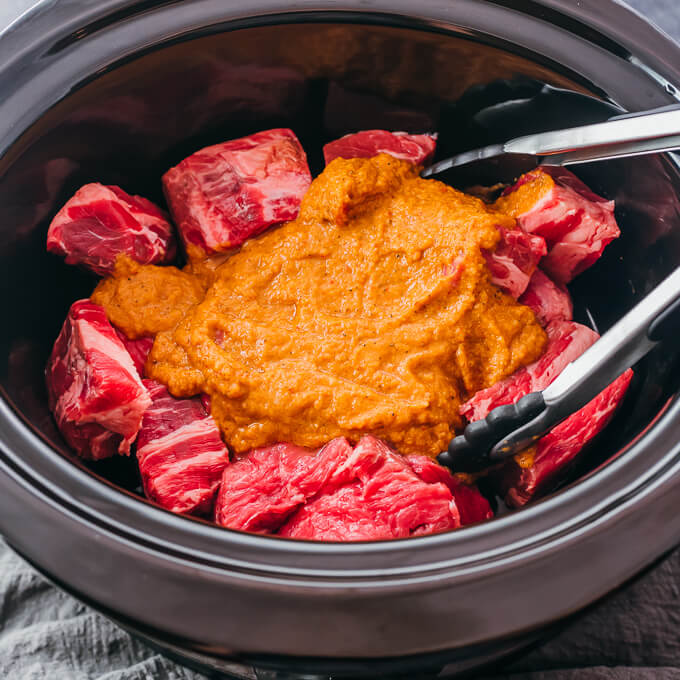 orange sauce over raw beef chunks