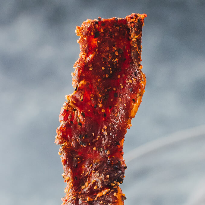 holding up single piece of beef jerky