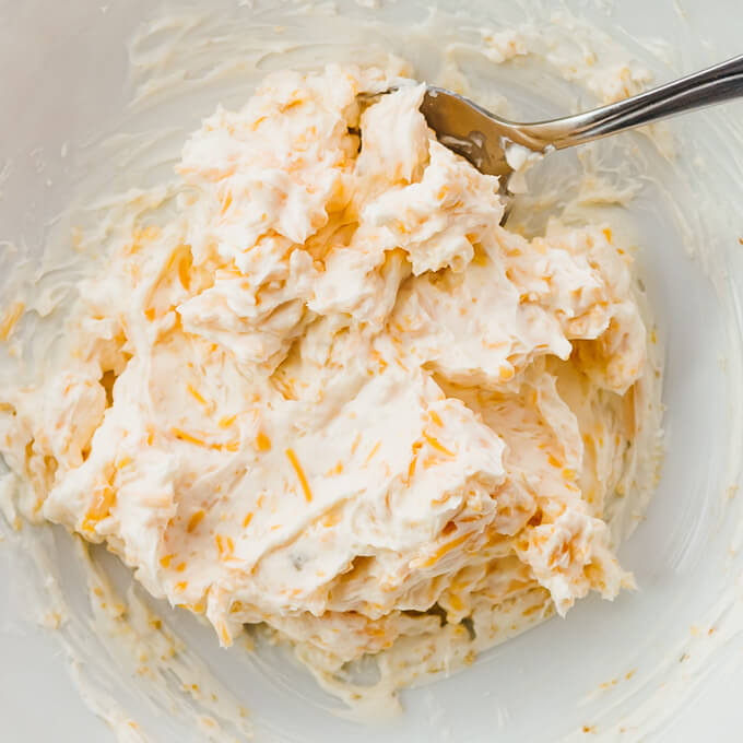 stirring cream cheese and cheddar together