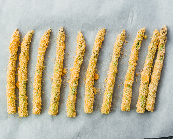 breaded asparagus spears on parchment paper