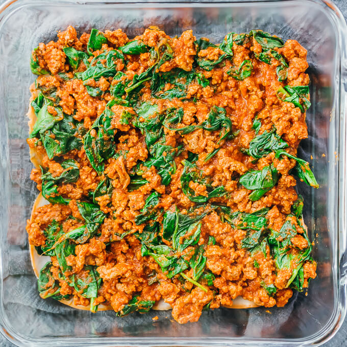 meat and spinach sauce in baking dish